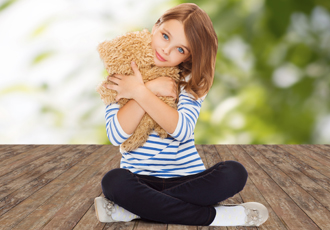 Girl comforted by her teddy bear